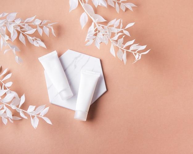 갈색 벽과 흰색 잎 장식 지점에 크림의 흰색 튜브