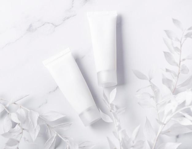 Белые тюбики крема на мраморном фоне и декоративная ветка с белыми листьями