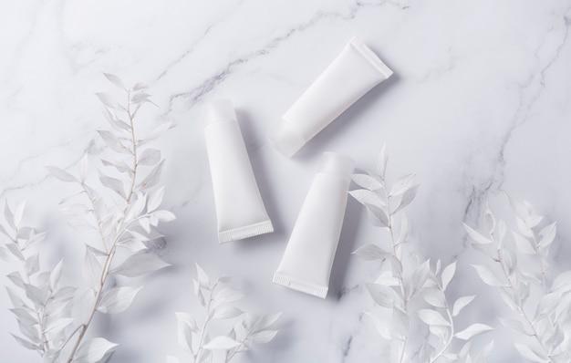 대리석 벽과 흰색 잎 장식 지점에 크림의 흰색 튜브