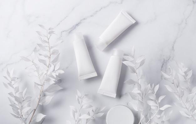 Белые тюбики крема на мраморной стене и декоративная ветка с белыми листьями