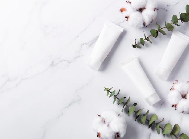 Белые тюбики крема на мраморной стене с цветами эвкалипта и хлопка