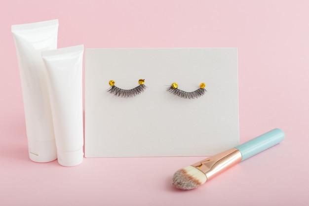 White tubes with mock up for design. false eyelashes, makeup brush on pink background.