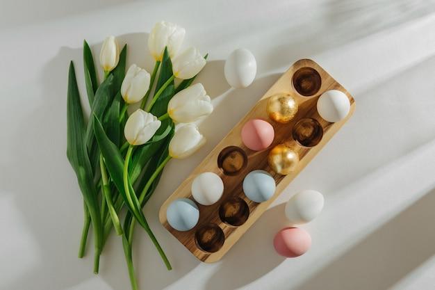 흰색 배경에 햇빛이 비치는 나무 달걀 상자에 있는 흰색 튤립과 달걀. 세련된 봄 작곡. 부활절 개념입니다.