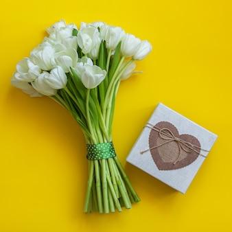 Белые тюльпаны и подарочная коробка на ярко-желтом фоне. концепция весны.
