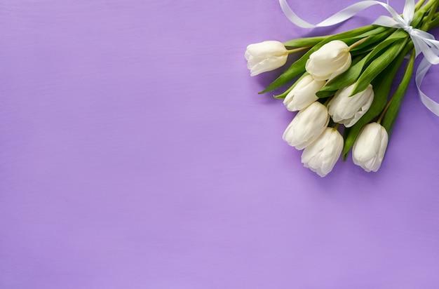 紫色の背景に白いチューリップの花束。春の花の背景上面図。コピースペース付きバナー