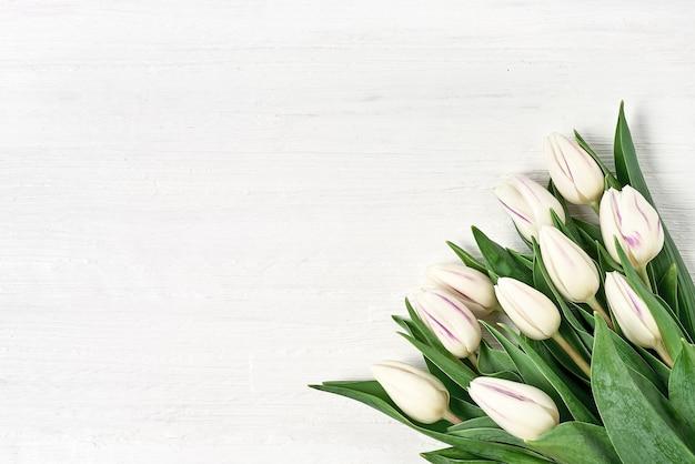 白い木製の背景に白いチューリップの花束。コピースペース、上面図