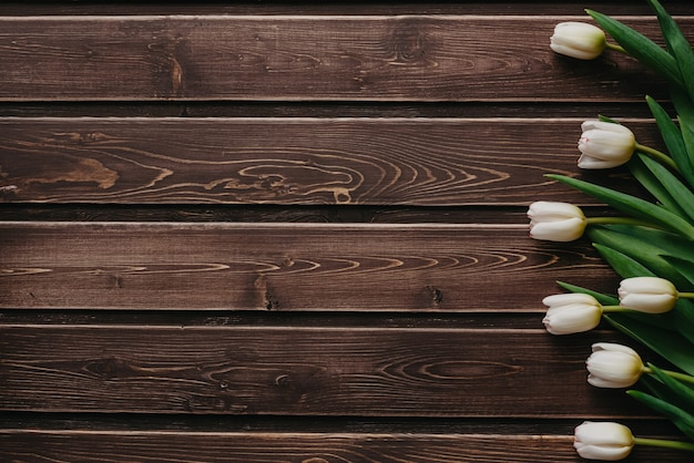 White tulips on a brown wooden background. blank greeting card for valentine's day