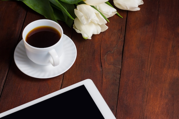 White tulips, a cup of coffee and a tablet on a dark wooden surface. concept of spring