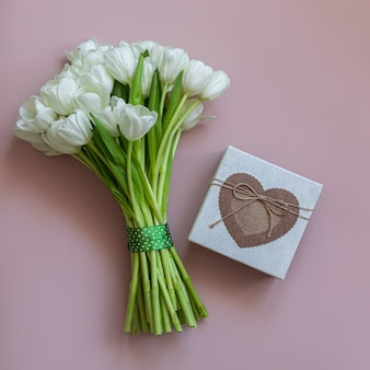 White tulips and gift box on pink background. spring concept.