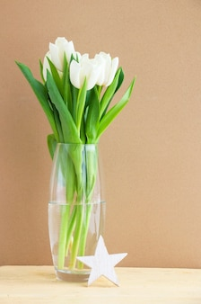 White tulips in a glass vase on a wooden table