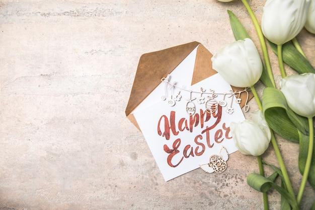 白いチューリップ、灰色の背景にハッピーイースターカード。上面図フラットレイ
