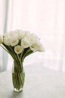 Белые тюльпаны в прозрачной вазе на цветном фоне. концепция весны. ретро зернистость пленки.