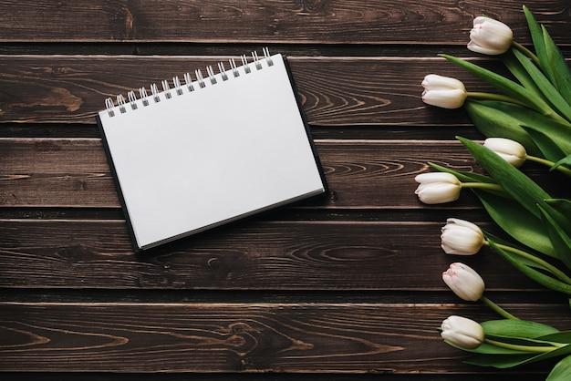 空のノートブックと木製のテーブルに白いチューリップ。フラット横たわっていた、トップビュー構成