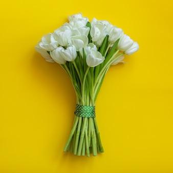 Белые тюльпаны на ярко-желтом фоне. концепция весны.