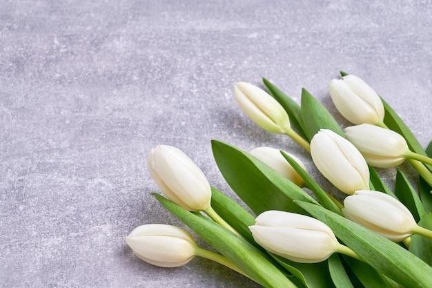 Белые тюльпаны на бетонном фоне. день рождения, день morthers, концепция дня святого валентина. праздничный фон, поздравительная открытка, копией пространства