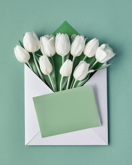 White tulips in paper envelope with decorative heart sticker on light green mint background