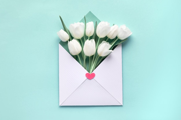 White tulips in white-green envelope on blue mint paper background, springtime flat lay