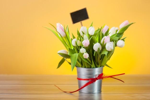 Белые тюльпаны с пустой этикеткой в горшке