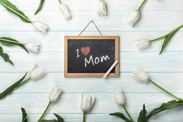White tulips with chalk board on blue wooden boards . mother's day