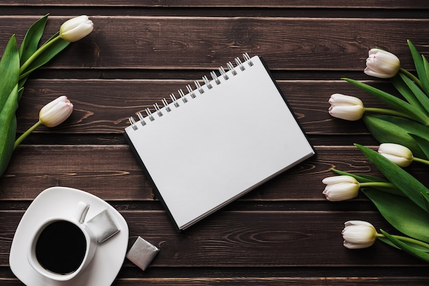 White tulips on a wooden table with a cup of coffee and an empty notebook