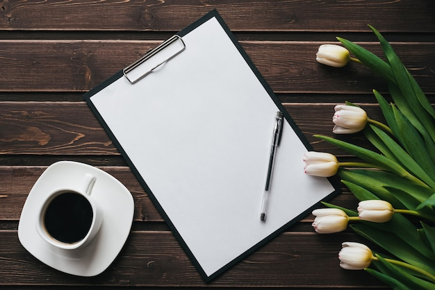 White tulips on a wooden table with a cup of coffee and an empty paper tablet