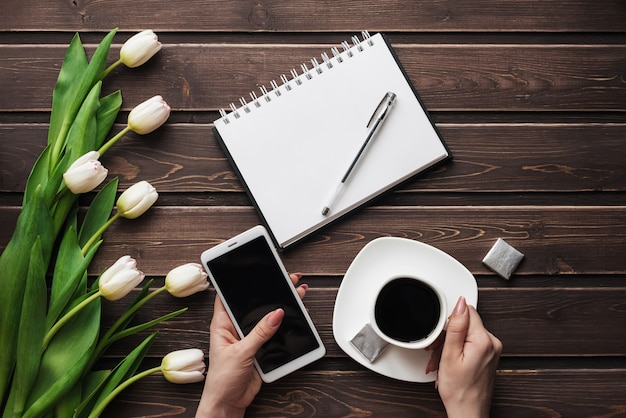 White tulips on a wooden table with an empty notebook, smartphone and a cup of coffee in women's hands