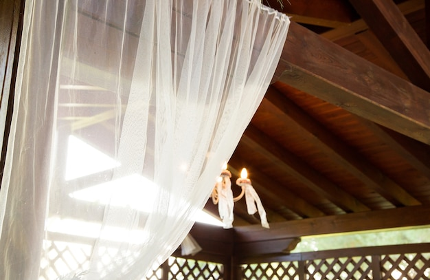 White tulle wooden roof and lit lamp detail
