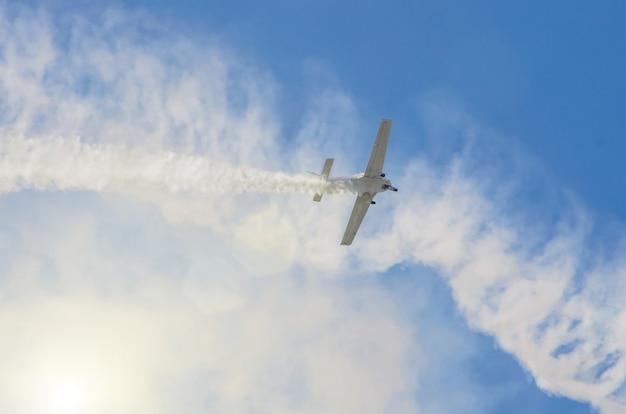 Белый турбовинтовой самолет со следом белого дыма на фоне голубого неба.
