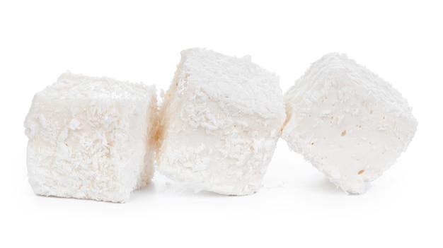 Белый рахат-лукум с кокосовой стружкой, изолированные на белом фоне Premium Фотографии
