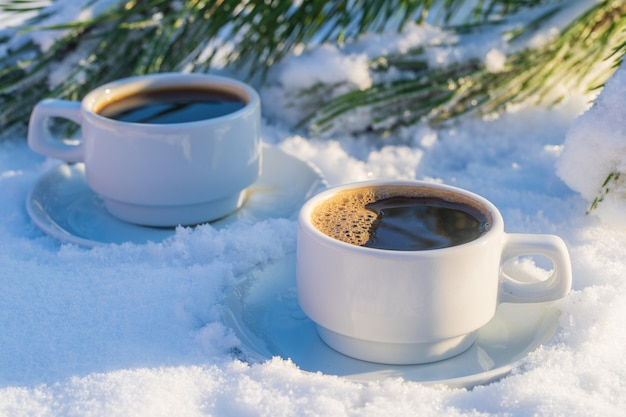 White two cup of hot coffee on a bed of snow and white background, close up. concept of christmas winter morning