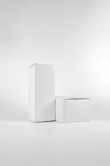 Две белые бумажные коробки - высокий и толстый лежали на белом фоне в студийной съемке с вырезками.