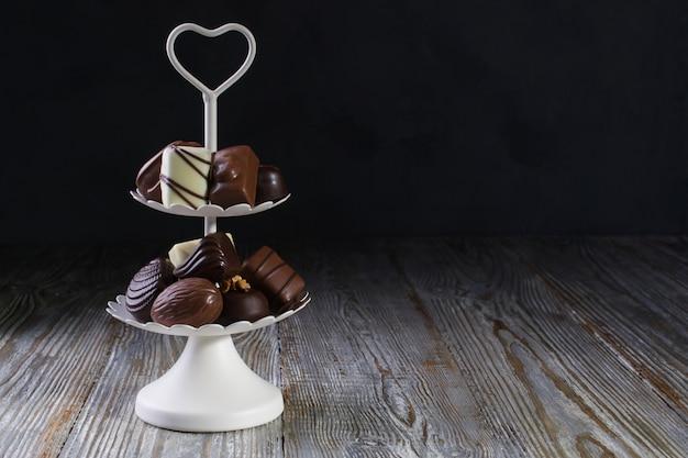 チョコレート菓子とプラリネの甘いお菓子がいっぱいの白い2層のサービングトレイ。コピースペース