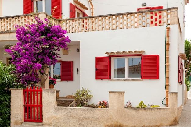 다양한 꽃 식물의 마당에 붉은 나무 셔터와 문이 있는 흰색 2층 집