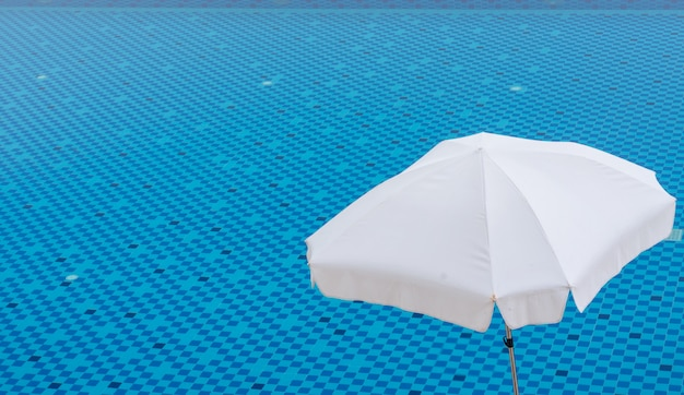 White umbrella on blue swimming pool