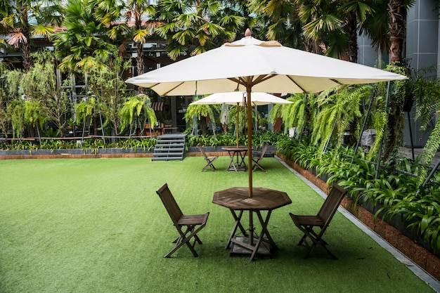 White umbrella within chairs and amazing garden in outdoor resort and hotel.