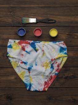 Белые трусы и краски для ткани на деревянной поверхности. окрашивание ткани в стиле «галстук-краситель».