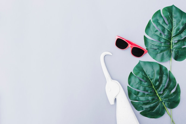 White unicorn, sunglasses and green monstera leaf over grey backdrop