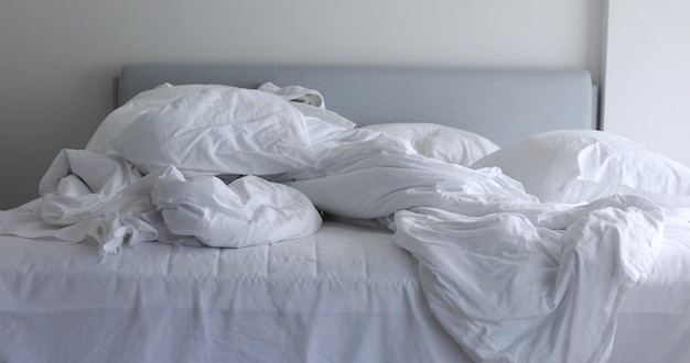 White unmade bed with crumpled messy blanket and pillow in morning light