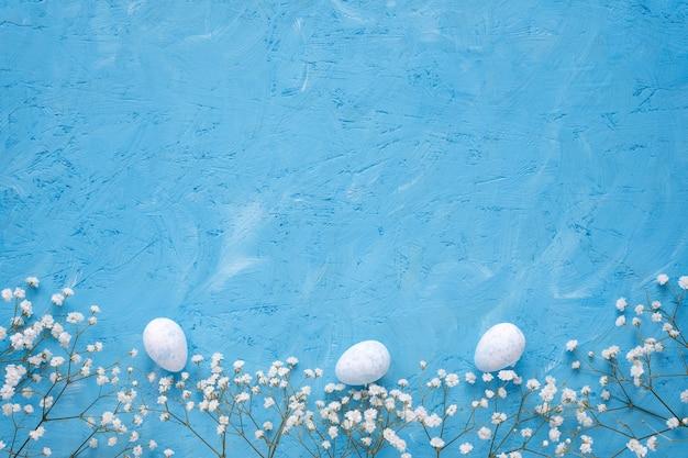 Белые неокрашенные пасхальные яйца и белые цветы на синем фоне, плоско