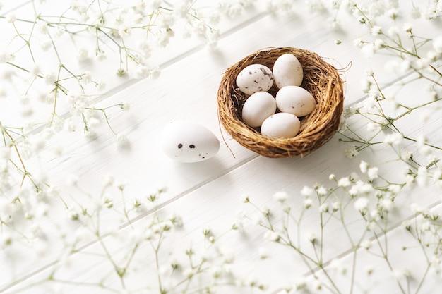 Белые неокрашенные пасхальные яйца и белые цветы на белом фоне.
