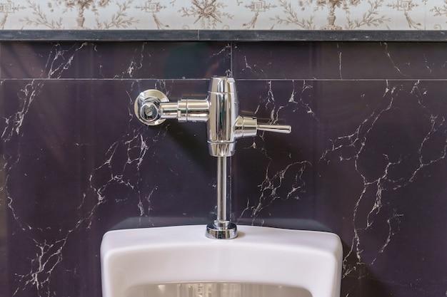 Белые писсуары в мужской ванной, белые керамические писсуары в общественном туалете