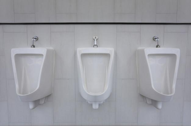 Белые писсуары в мужской ванной комнате внутренней отделки.