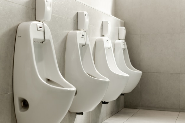 White urinals in a row in men public toilet.