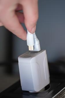 Ricarica usb bianca per gadget su uno sfondo sfocato del primo piano della stanza