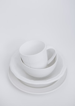 White utensils three plates and a cup on a white background