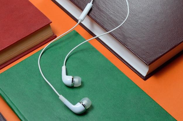 Белые вакуумные наушники лежат на книгах, разложенных на оранжевой поверхности