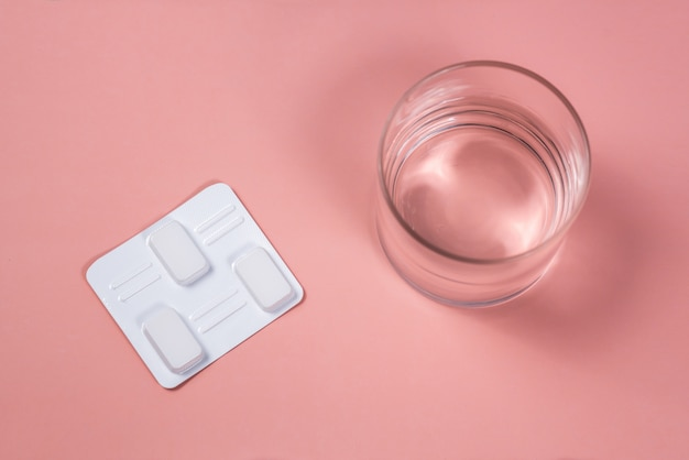 White vaginal antibacterial pills on pink background.candles are soaked in water and injected into vagina to treat candidiasis, thrush, inflammation. effective modern drug for treatment of diseases