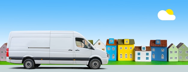 흰색 밴은 푸른 하늘 배경에 다채로운 미니어처 주택을 따라 운전합니다.