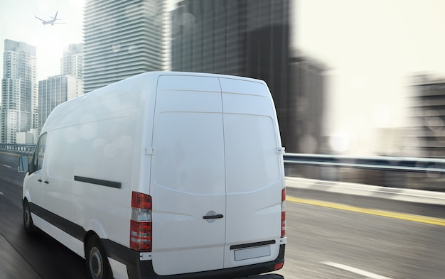 White van moving fast on the highway with a modern city