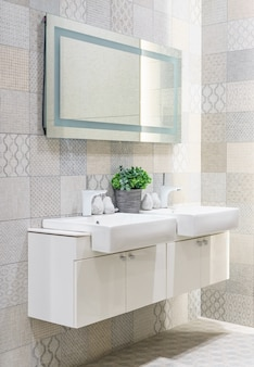 White vanity top with two sinks and a stylish mirror in bathroom interior